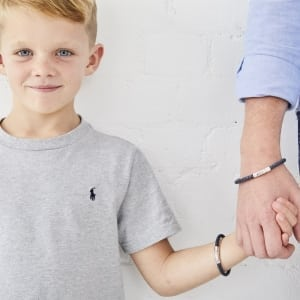 young boy and dad with matching leather bracelets